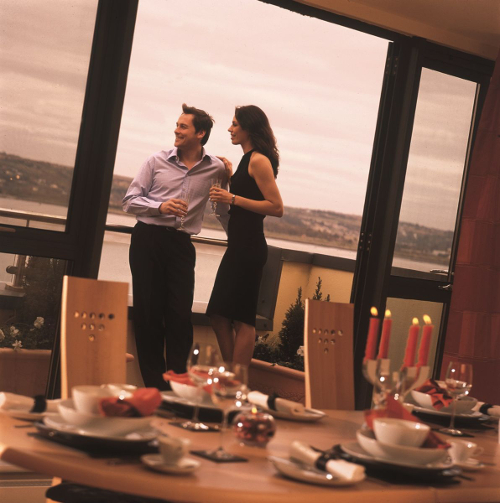 Photograph of couple at window in dining room at Hartys Quay Apartments