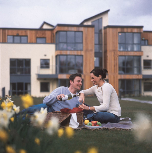 Photograph of couple enjoying picnic on lawn at Hartys Quay Apartments