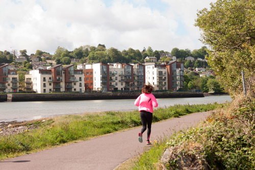 Photograph of jogger with Hartys Quay Apartments in background