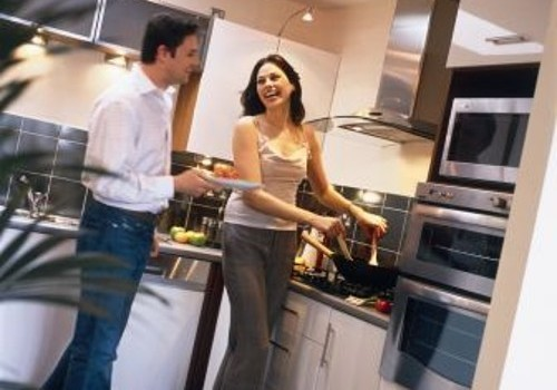 Photograph of couple in kitchen cooking at Hartys Quay Apartments