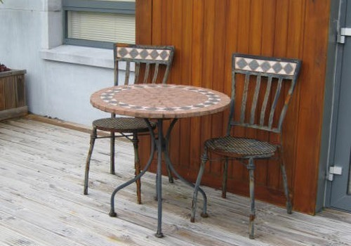 Photograph of patio with table and two chairs at Hartys Quay Apartments