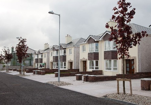 Photograph of six semi detached houses at Jacobs Island with copper leaved trees